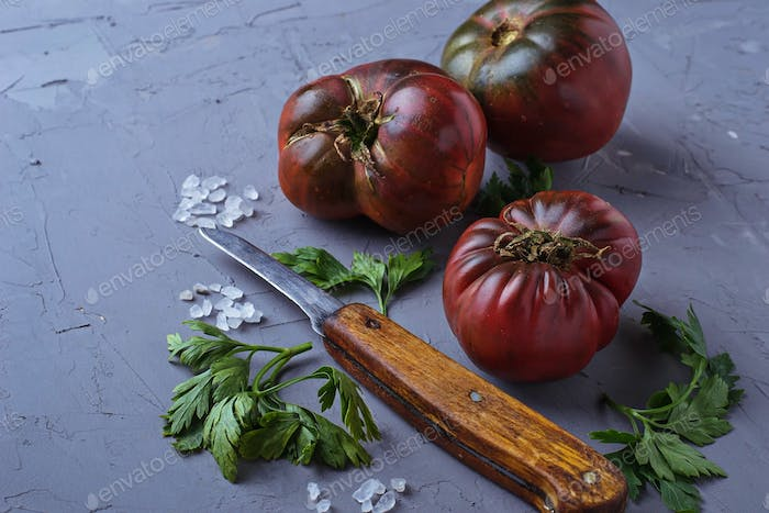 Tomato, salt, parsley and knife on gray concrete background