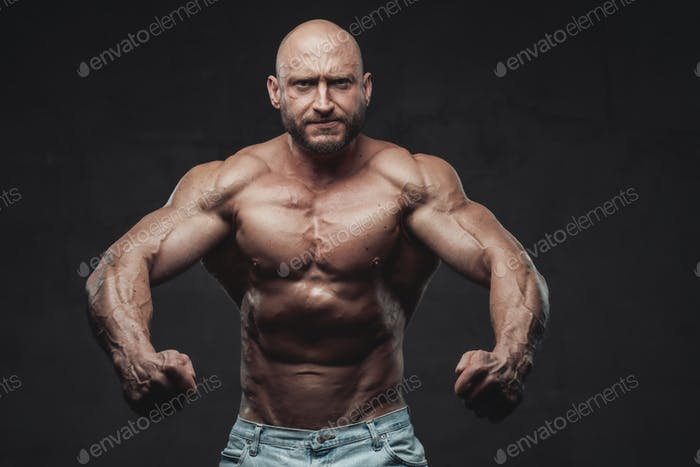 Serious bald bodybuilder posing in dark background with naked torso