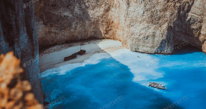 Navagio beach panoramic shot in moody vintage waved bay water and abandoned shipwreck on shore