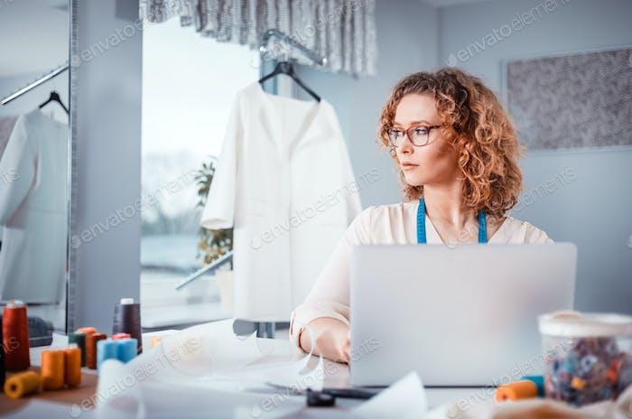 Tailor using laptop, modern fashion designer at workshop