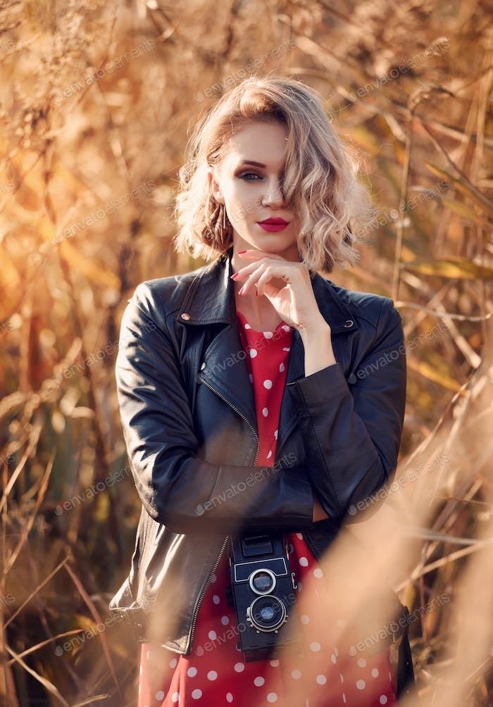 Beautiful young blonde woman with the retro camera
