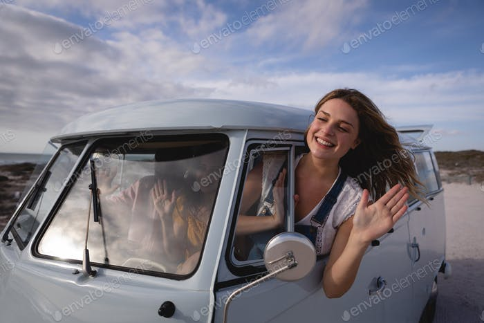 oman having his head outside the camper van while she is waving out by window