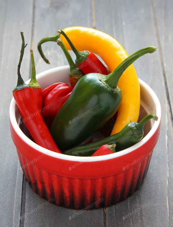 Hot chili peppers in bowl on wooden background
