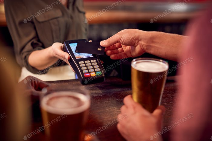 Close Up Of Man Paying For Drinks At Bar Using Contactless Card