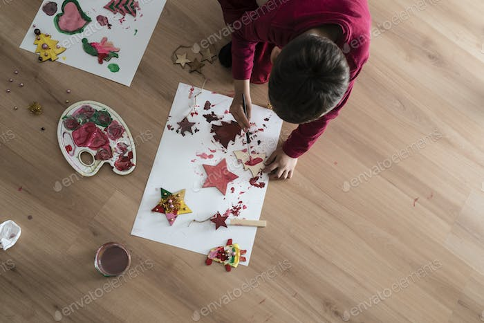 A kid doing Christmas painting decorations