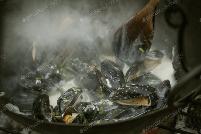 Chef cooking Black Mussels over a barbecue.