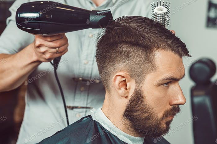 Thumbnail for The hands of young barber making haircut to attractive man in barbershop