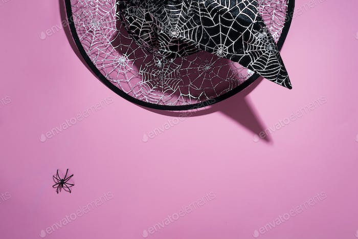 Black witch hat with a pattern of cobwebs and spider on pink background, flat lay with copy space