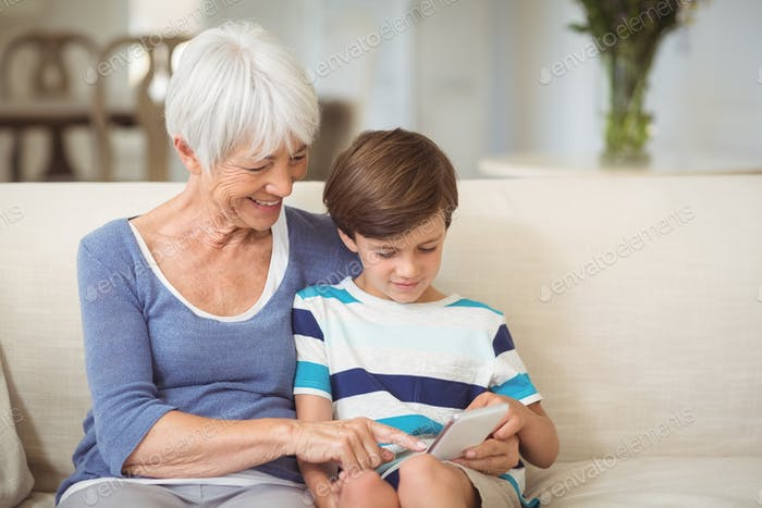 Grandson and grandmother using mobile phone in living room
