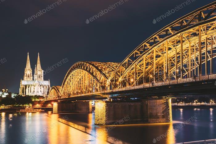 Köln, Deutschland. Nachtansicht Auf Den Kölner Dom Und Die Hohenzollernbrücke. Gotische Kathedrale In Der Dämmerung