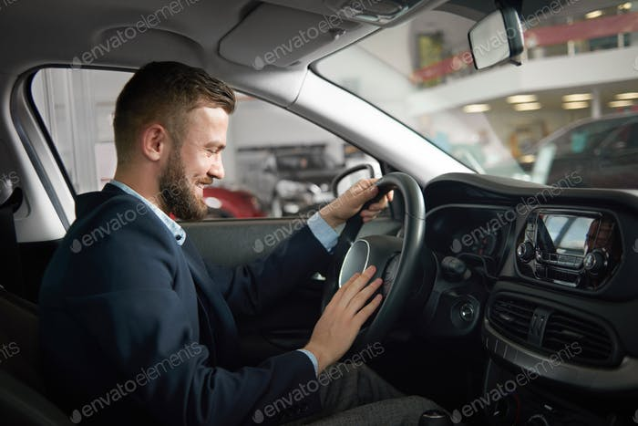 Man sitting in car holding hands on steering wheel