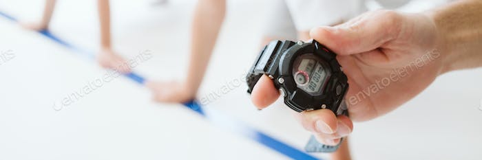 Trainer measures the time of children during the school race