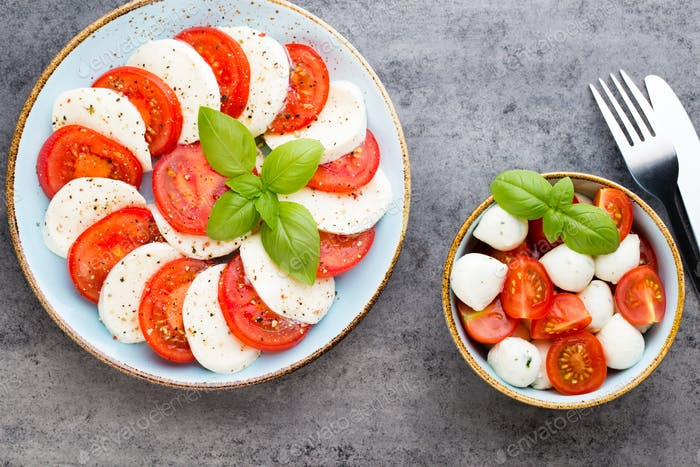 Tomatoes, mozzarella cheese, basil and spices on gray slate stone chalkboard.