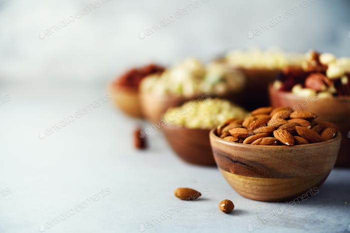 Almond nuts in wooden bowl. Food mix background, top view, copy space, banner. Assortment of nuts -