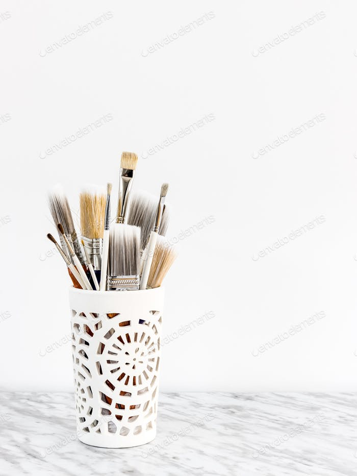 Paintbrushes in a decorative vase on marble surface