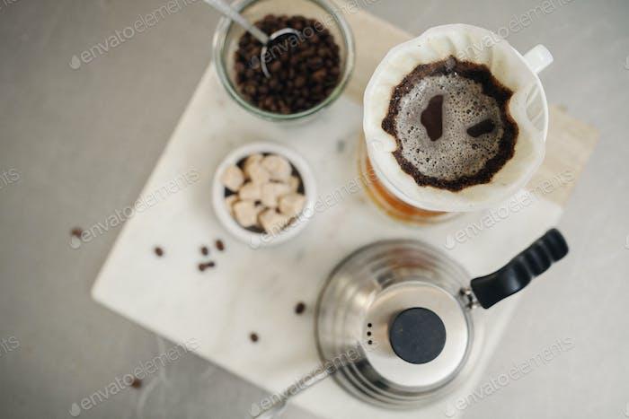 Haciendo café de filtro. Vista aérea de café molido, filtro de papel y terrones de azúcar.