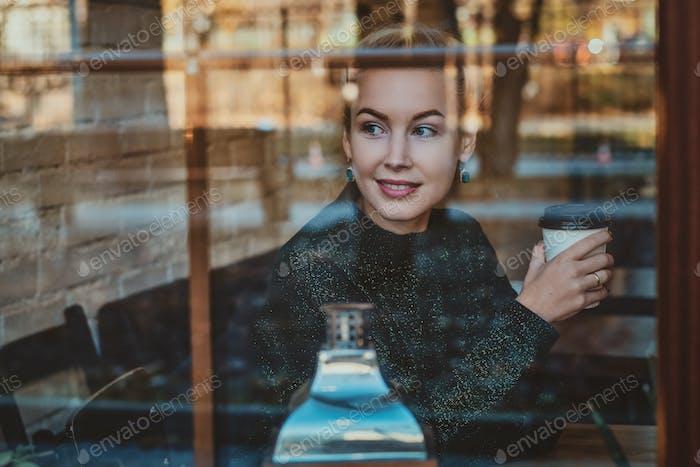 Hübsche Frau trinkt Getränk im Café