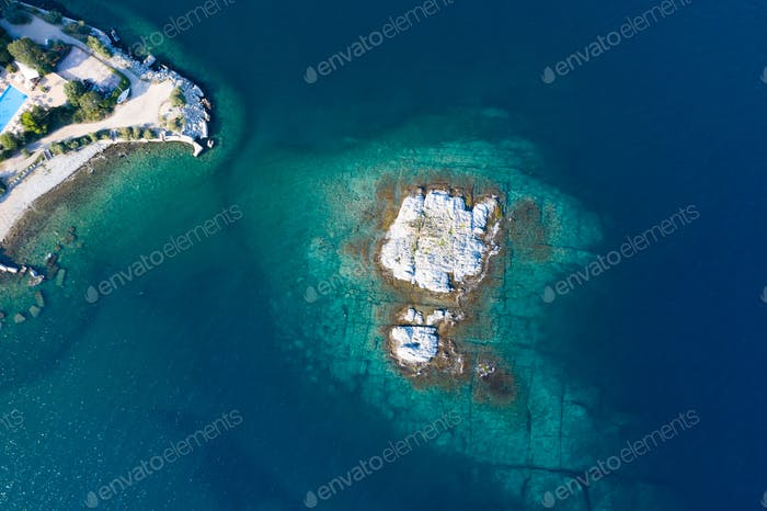Aerial drone view of a remote rocky island in open sea.