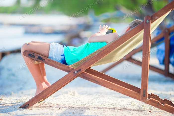 Adorable little girl relaxing in colorful wooden chair at beach during summer vacation