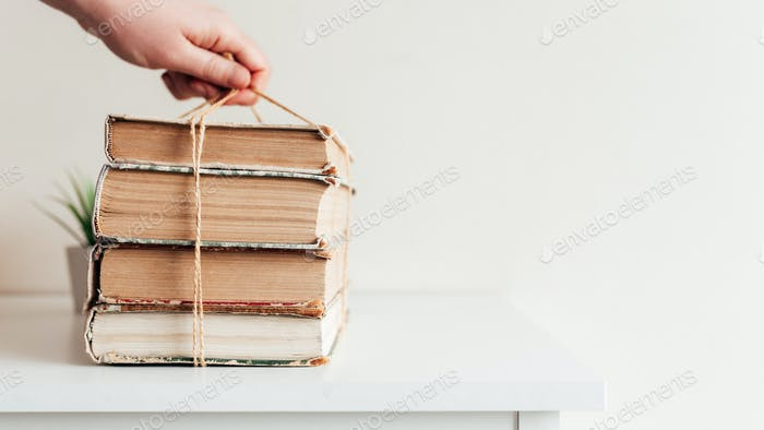 Hand holding books, concept of learning, education, science, wisdom, knowledge