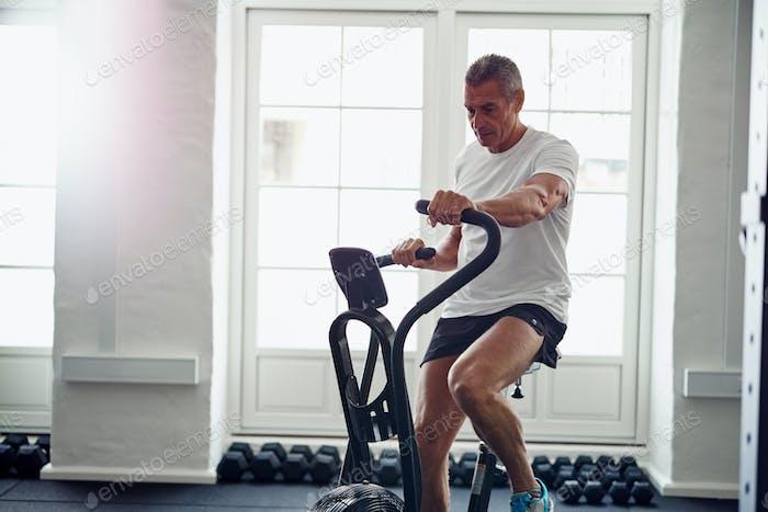 Reifer Mann Reiten ein Gesundheitsclub stationäre Fahrrad