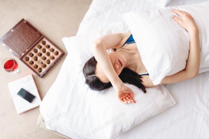 Woman lies under the blanket, top view, depression