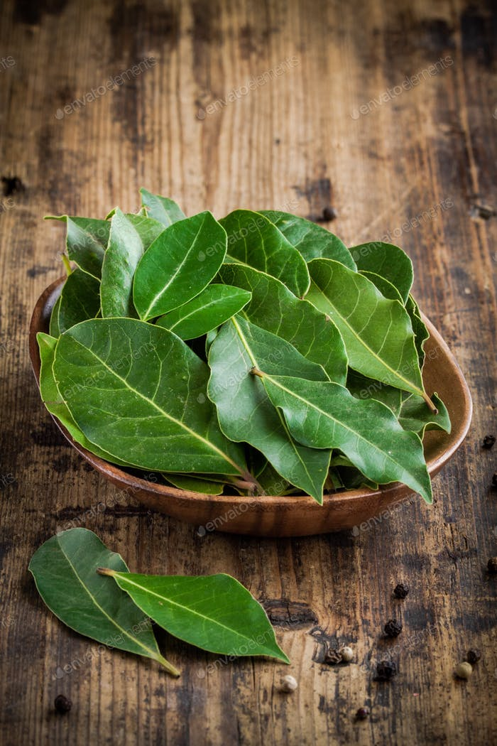 Fresh bay leaves in a wooden bowl on a wooden background