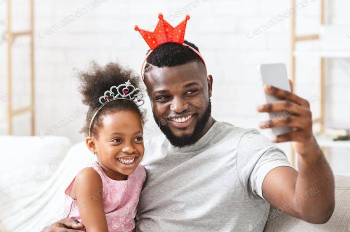 Joyful afro family having fun at home, taking selfie