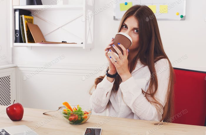 Woman has healthy business lunch in modern office interior