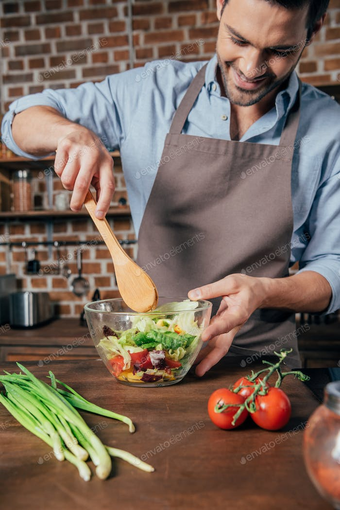 happy young man mixing salad