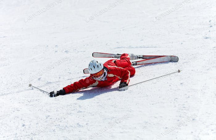 Female skier looking at camera after falling down on slope
