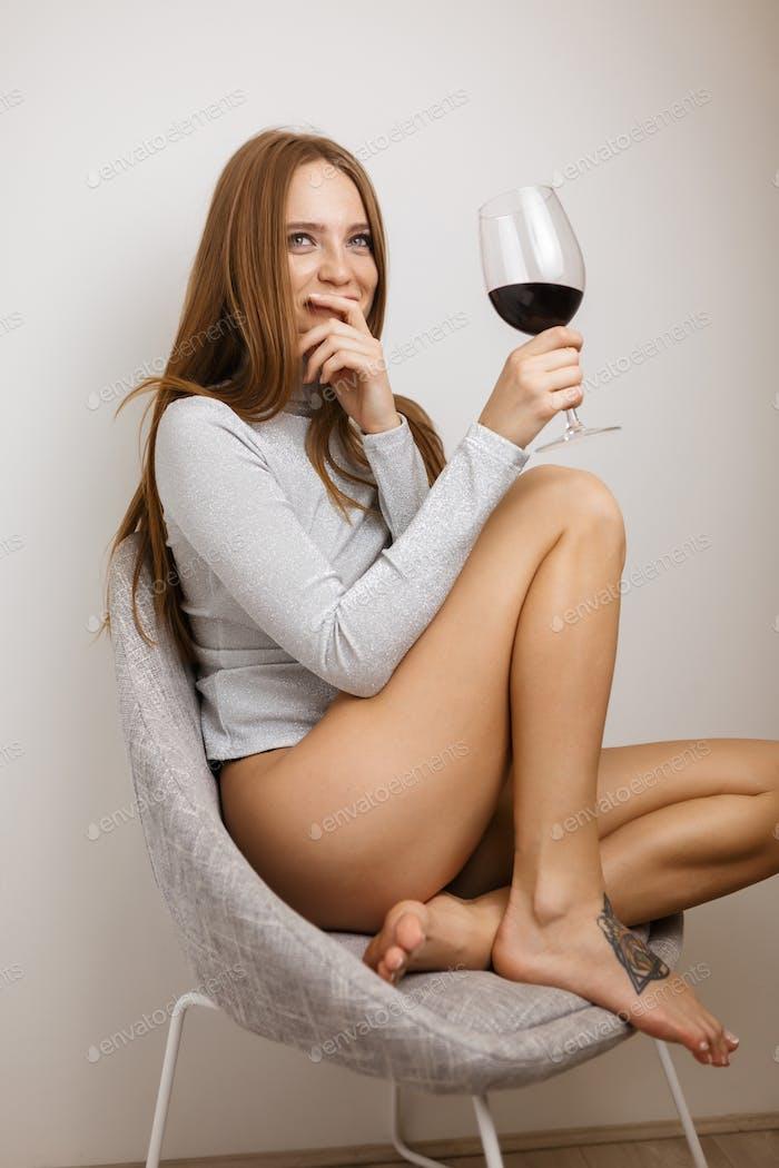 Hübsches Mädchen sitzen im Stuhl mit Glas Rotwein in der Hand glücklich beiseite auf grauen Hintergrund