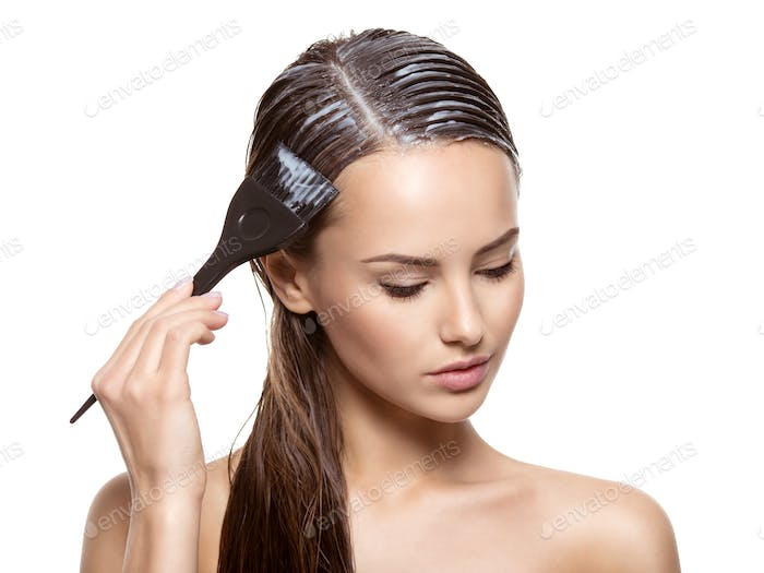 Young woman  coloring hair with brush
