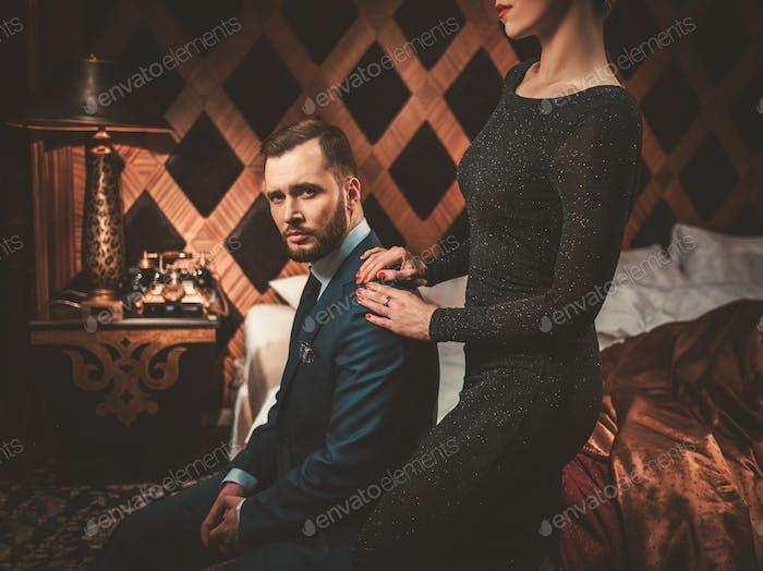 Gut gekleidetes Paar im luxuriösen Schlafzimmer Interieur.
