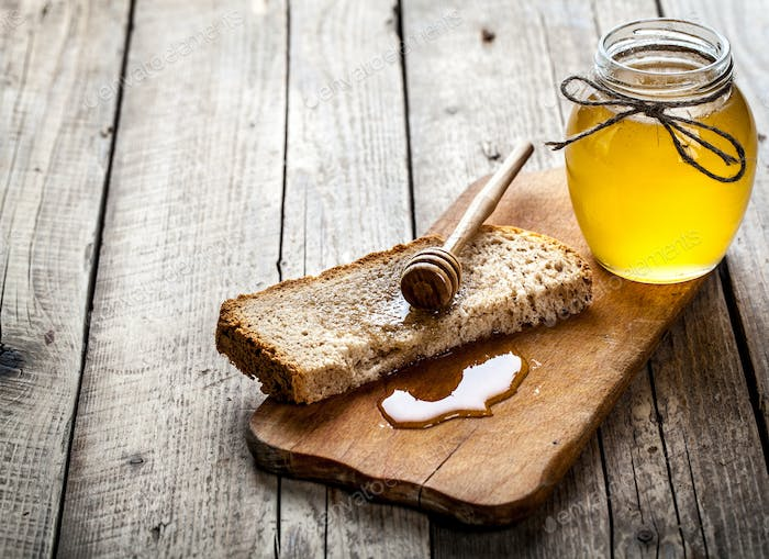 Honey in a jar, slice of bread, wheat on an old vintage planked wood table