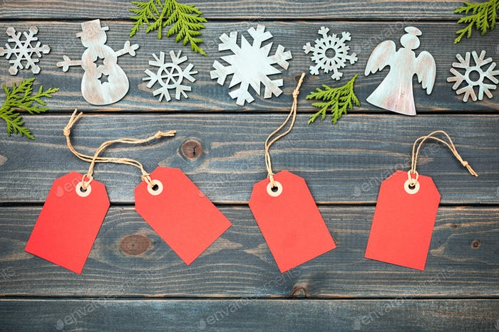 Christmas decoration and red gift tags on wooden background