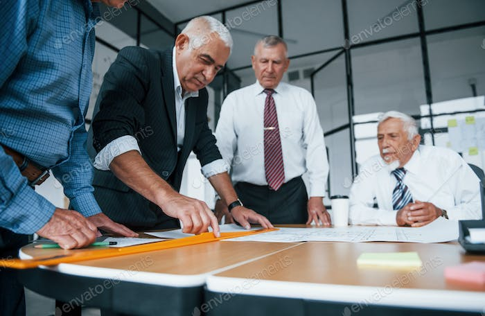 Aged team of elderly businessman architects have a meeting in the office