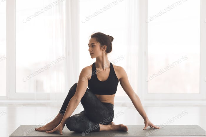 Fit girl practicing yoga looking at copy space