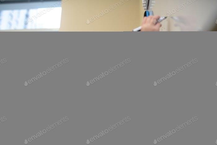 Alumno pensando qué escribir en la pizarra blanca