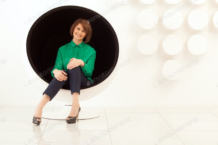 Attractive woman sitting on spherical chair with hands on knees