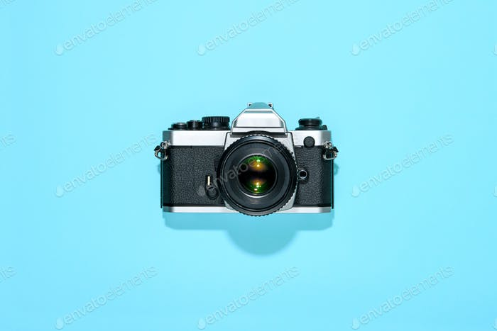 Classic vintage reflex camera centered on blue
