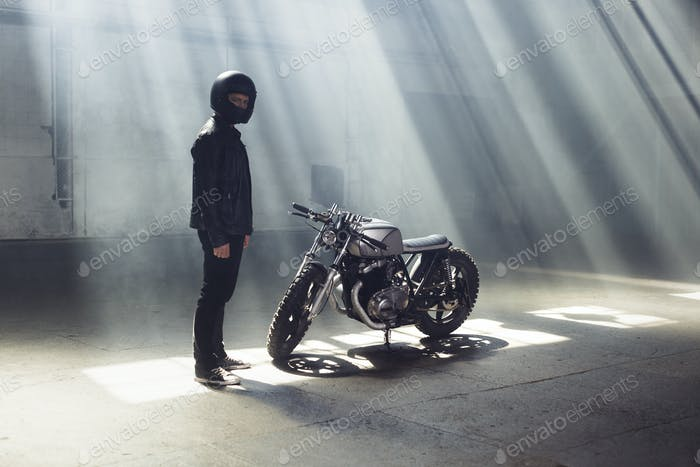 biker wearing jeans and leather jacket standing with motorcycle