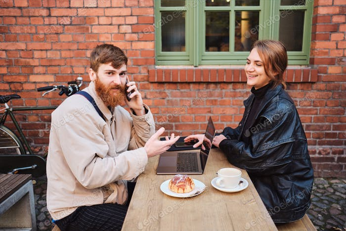 Young couple joyfully working together during coffee break in street cafe