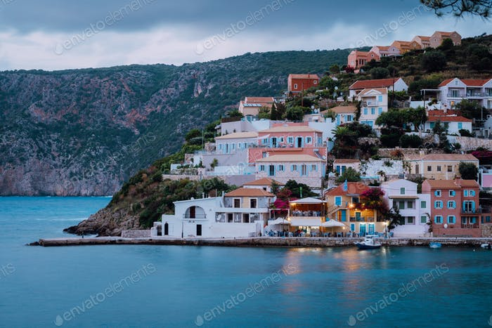 Assos town in evening twilight. Vivid colorful local house buildings at hill. Kefalonia, Greece