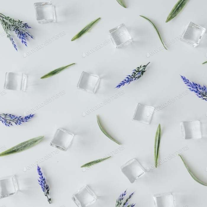 Creative pattern of ice cubes , leaves and flowers on bright background. Flat lay summer