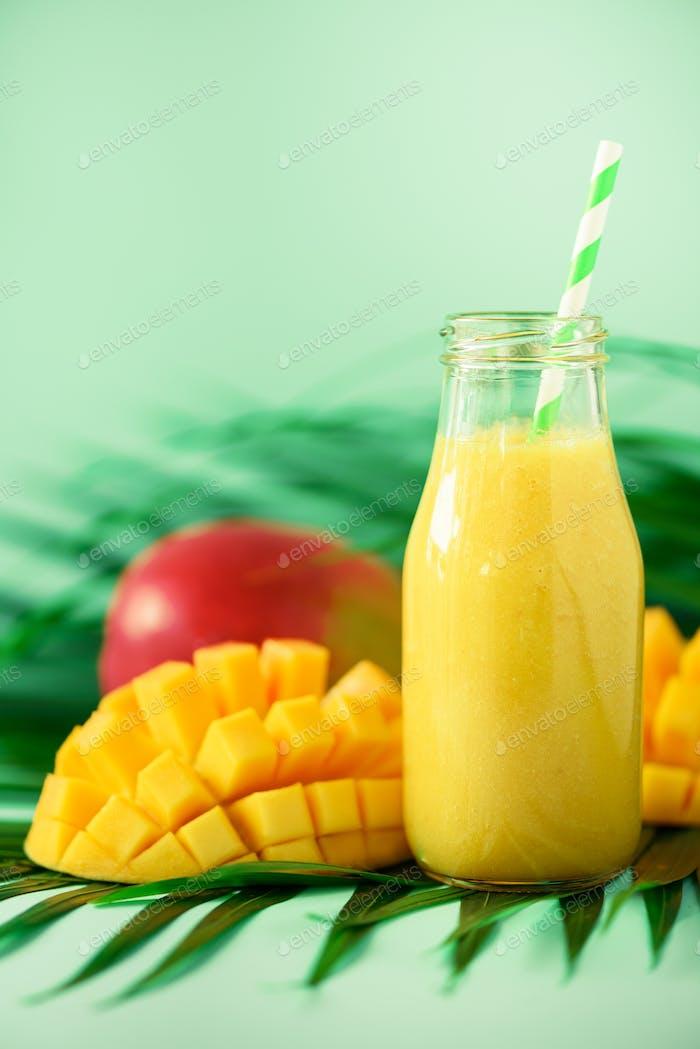 Köstlicher saftiger Smoothie mit Orangenfrucht und Mango auf türkis Hintergrund. Kopierraum. Pop Art