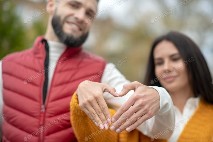 Selective focus of hands in the heart shape