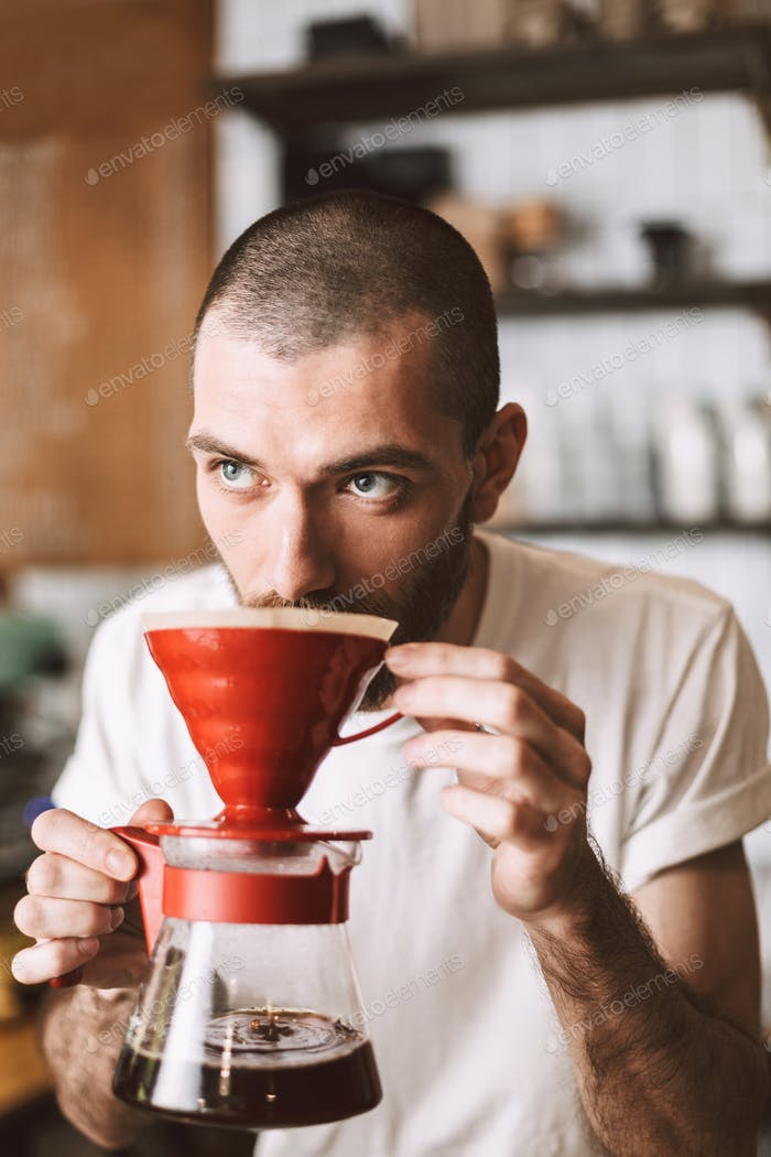 Young barista smelling pour over coffee thoughtfully looking aside in cafe at bar counter