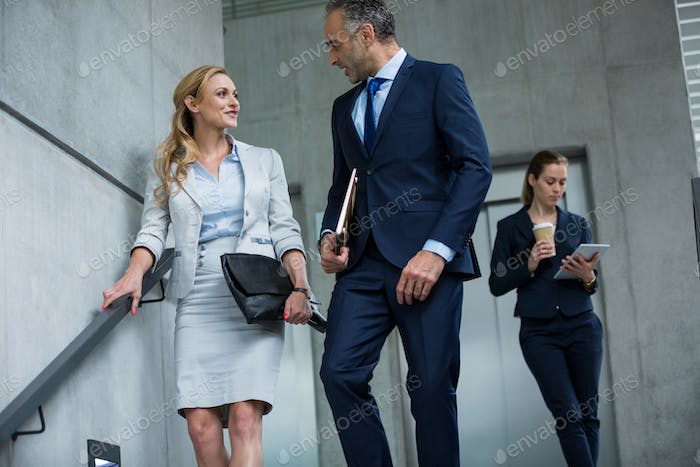 Business colleagues talking to each other while walking down stairs