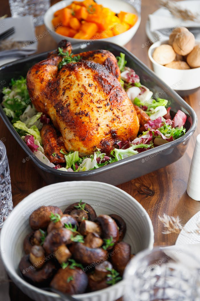 Decorated festive table with whole roasted chicken